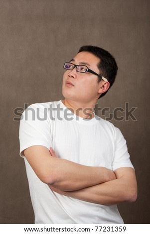 portrait of a young asian man in a white t-shirt with crossed arms looking up on grey background - stock photo