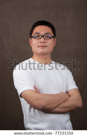 portrait of a young asian man in a white t-shirt with crossed arms on grey background - stock photo