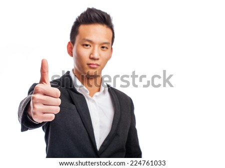 portrait of a young asian man with thumb up - stock photo