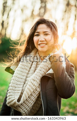 Portrait of a young Asian woman at the park in the late afternoon on an autumn day - stock photo