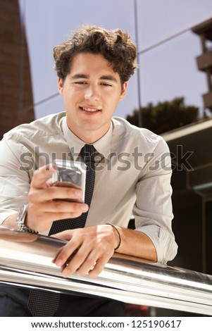 Portrait of a young aspirational businessman using a smart phone while leaning on a banister outside a modern glass office building in the city. - stock photo