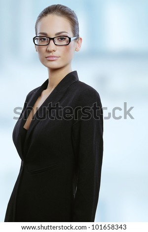 Portrait of a young attractive business woman in glasses - stock photo