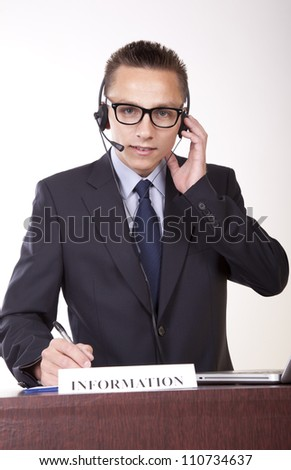 Portrait of a young attractive male receptionist working at the information desk. - stock photo