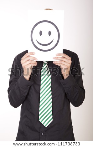 Portrait of a young attractive man holding a smiley face. - stock photo