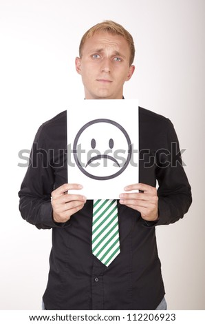 Portrait of a young attractive man holding sad smiley face. - stock photo