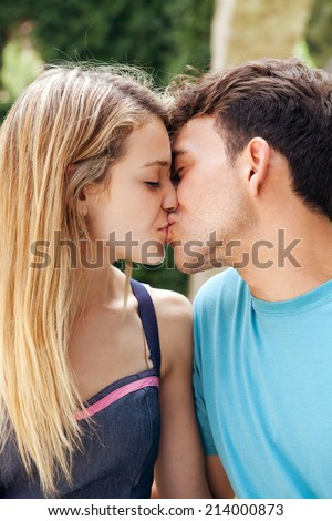 Portrait of a young attractive romantic couple kissing and enjoying a day out together, outdoors. Romance lovers and relationships. - stock photo
