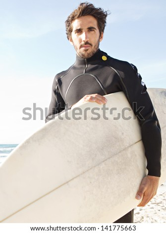 Portrait of a young attractive surfer standing on a white sand beach while carrying his surfing board under his arm during a sunny day against an intense blue sky. - stock photo