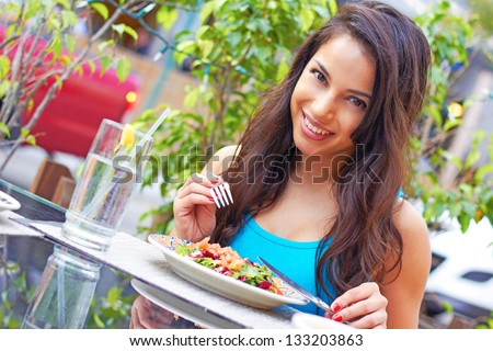 Portrait of a young attractive woman eating salad at cafe table. Horizontal shot.Beautiful young female enjoying a fresh salad at a nice restaurant. Cute hispanic girl eating a healthy meal. - stock photo
