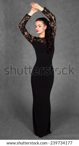 Portrait of a young attractive woman in a black evening dress over grey background - stock photo