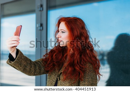 Portrait of a young attractive woman making selfie photo on pink smartphone  - stock photo