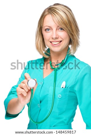 Portrait of a young attractive woman wearing doctor uniform and holding stethoscope, isolated over white - stock photo