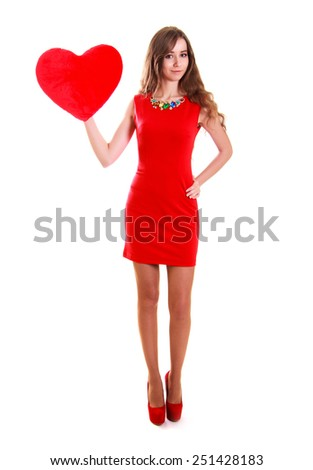 Portrait of a young attractive woman with a heart-shaped pillow isolated over white background - stock photo