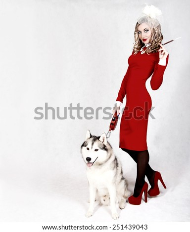 Portrait of a young attractive woman with a husky dog over grey background - stock photo