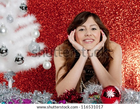 Portrait of a young attractive woman with a small christmas tree and ornaments sitting at a table in front of a red glitter background. - stock photo