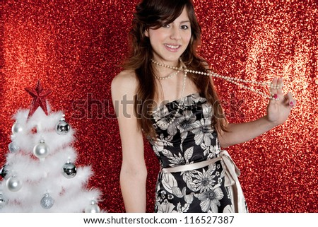 Portrait of a young attractive woman with a small christmas tree pulling her pearls necklace while standing in front of a red glitter background. - stock photo