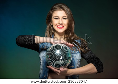 Portrait of a young attractive woman with mirror ball on a color background. - stock photo