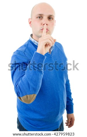 portrait of a young bald man making a shushing gesture with his finger, isolated on a white studio background. - stock photo