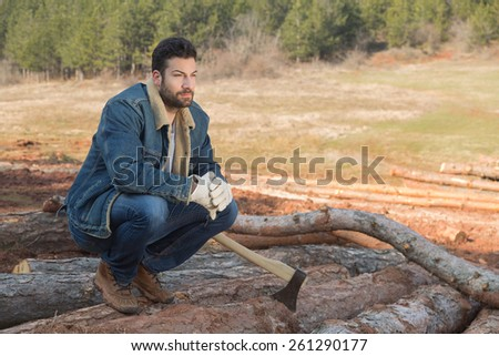 Portrait of a young bearded and attractive lumber-sexual man posing in the forest. - stock photo