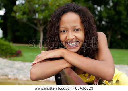 Portrait of a young beautiful african american woman sitting on a bench - stock photo