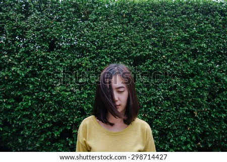 Portrait of a young beautiful asian woman unhappy on trees background, vintage style - stock photo
