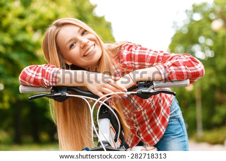 Portrait of a young beautiful blond girl leaning on a handlebar of her bike smiling and posing, wearing a red checkered shirt in a green park - stock photo