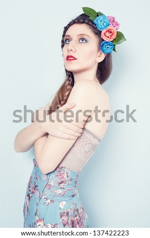 portrait of a young beautiful blue eyed model on blue background with a circlet made of flowers on her head - stock photo