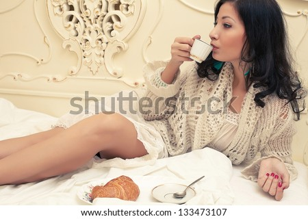 Portrait of a young beautiful brunette having breakfast (tea (coffee), croissants) and posing on a bed in her vintage bedroom. Copy-space. Indoor shot - stock photo