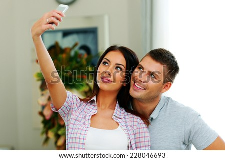 Portrait of a young beautiful couple making selfie photo with smarphone - stock photo