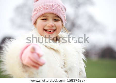 Portrait of a young beautiful girl child wearing a winter coat and hat while visiting a park during a cold winter day, smiling and pointing to the camera with her hand. - stock photo