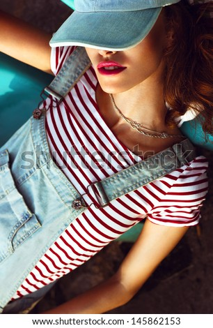 Portrait of a young beautiful girl with red lips and a denim suit, resting outdoors - stock photo