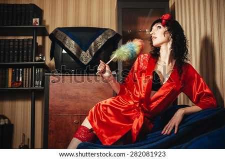 Portrait of a young beautiful housewife playing with a duster and smiling. - stock photo