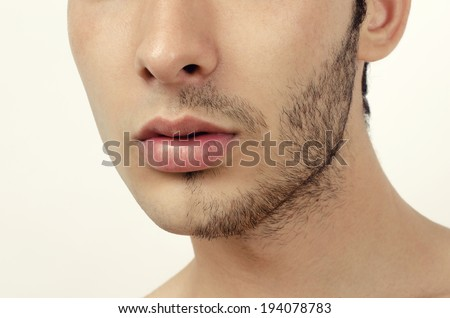Portrait of a young beautiful man with half face shaved - stock photo