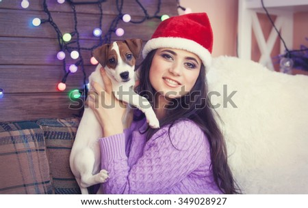 portrait of a young beautiful smiling woman in Santa Claus hat with jack russell terrier puppy - stock photo