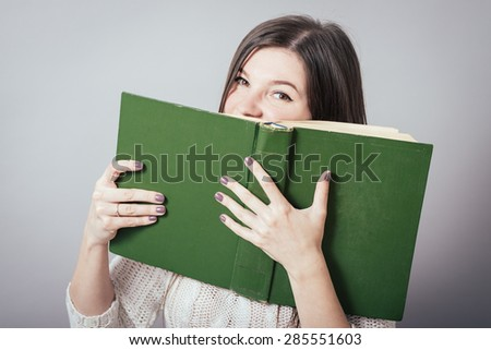 Portrait of a young beautiful student with university building in the background. She is holding books in hands. - stock photo