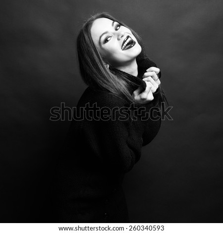 Portrait of a young beautiful stylish woman against black background - stock photo