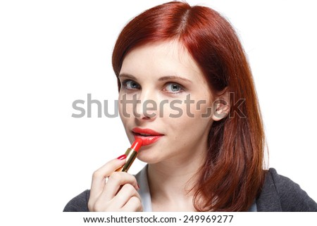 Portrait of a young beautiful woman applying  lipstick for lips on a white background. - stock photo