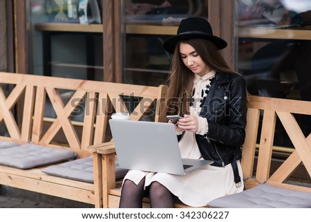 Portrait of a young beautiful woman dressed in with style using mobile phone during work on portable laptop computer, female freelancer chatting on cell telephone while sitting with net-book outdoors - stock photo
