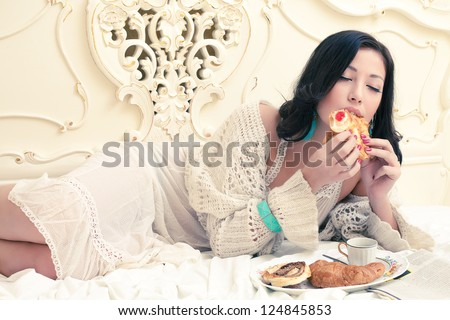 Portrait of a young beautiful woman eating her croissant with strawberry jam and getting pleasure in a vintage bedroom. Indoor shot - stock photo