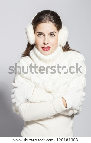 portrait of a young beautiful  woman in white winter look. on grey background. - stock photo