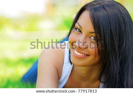 Portrait of a young beautiful woman lying on the grass and smiling - stock photo