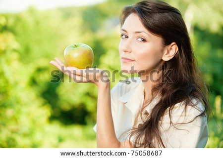 Portrait of a young beautiful woman with green apple on a background nature - stock photo