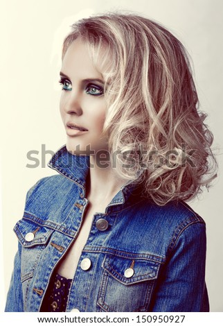 portrait of a young beautiful woman with loose curly hair blond hair wearing blue jean jacket with retro effect - stock photo