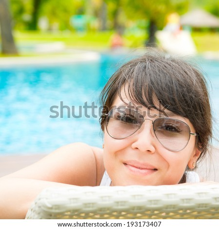 Portrait of a young beautiful woman with sunglasses lying on a sun lounger on against of the pool background - stock photo
