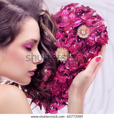 Portrait of a young beauty with rose heart - stock photo