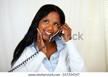 Portrait of a young black lady thinking and conversing on phone - stock photo
