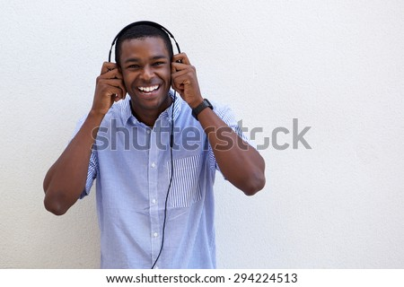 Portrait of a young black man laughing with headphones on white background - stock photo