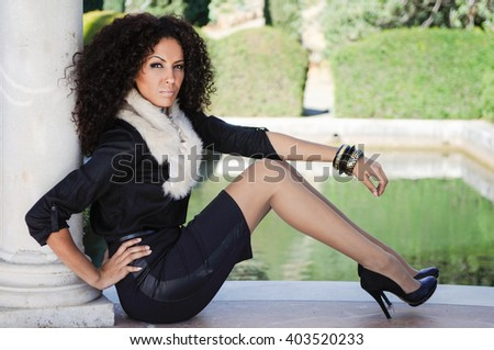 Portrait of a young black woman, afro hairstyle, in urban background. Girl with elegant clothes and bracelet. - stock photo