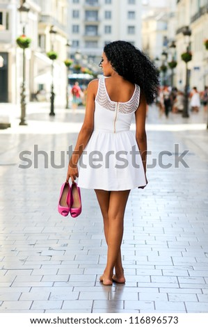 Portrait of a young black woman, afro hairstyle, walking barefoot on a commercial street - stock photo