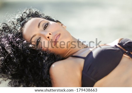 Portrait of a young black woman, afro hairstyle, wearing bikini - stock photo