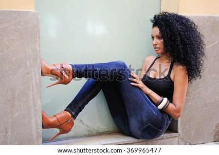 Portrait of a young black woman, afro hairstyle, wearing blue jeans in urban background - stock photo